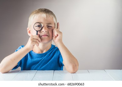 Curious boy with a clever face looks through the magnifying glass and lifts his index finger up. The concept of logical thinking.