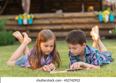 curious boy and a girl lying on the grass in the summer yard and read a book