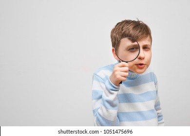 Curious boy looking intently through magnifying glass on white background.  Research, exploration, guessing concept