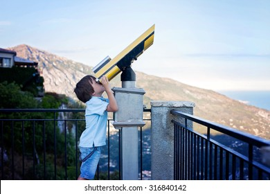 Curious boy, looking through a telescope at something interesting, summertime