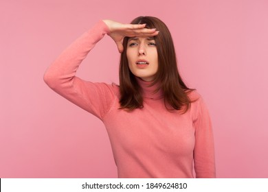 Curious brunette woman in pink sweater looking far away with hand over head, trying to see something, bad vision. Indoor studio shot isolated on pink background