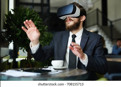 Curious businessman looking at 3d virtual reality in goggles