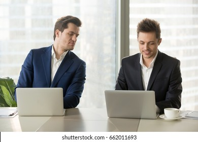 Curious businessman secretly looking at laptop screen of colleague, sneaking peek at other computer, stealing idea, copying private information on exam, nosy clerk spying on coworker at workplace