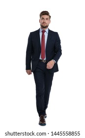 Curious businessman stepping forward and looking up while wearing a blue suit and red tie on white studio background