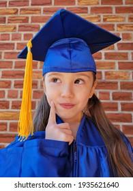 Curious Caucasian girl in a graduation gown. Brick background.  graduation 2021