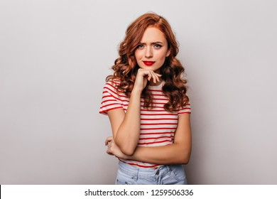 Curious caucasian girl with long wavy hair posing in studio. Indoor photo of wonderful ginger woman isolated on light background.