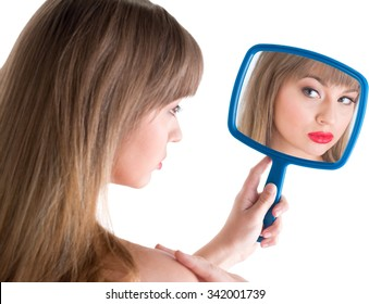 Curious Caucasian young woman medium brown using hand mirror - Isolated