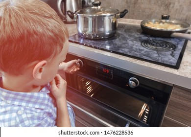 Curious child playing with the knobs on the oven. Danger for children at kitchen.