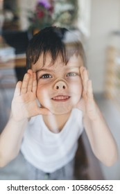 Curious child standing behind the glass and pressing his nose on a glass window