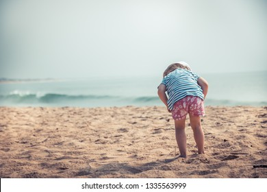 Curious child toddler exploring beach childhood travel lifestyle with copy space vintage style