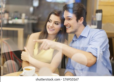Curious couple looking away through window in cafe