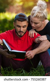 Curious couple of students -  young man with stubble and beautiful blond woman looking into book while relaxing in the park