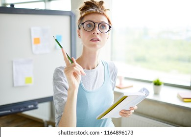 Curious creative student girl in glasses having idea for new project when analyzing notes in diary, she standing in modern office