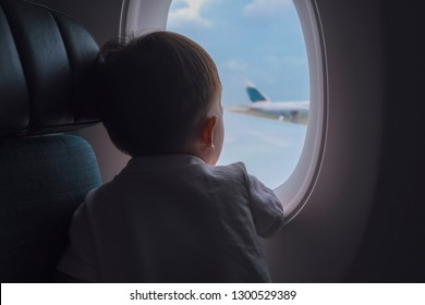 Curious cute little Asian 2 -3 years old toddler baby boy child looking out from airplane window during flight on airplane. Flying with children, Happy air travel with kids & little traveler concept