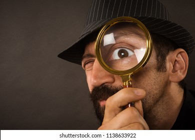The curious detective is looking with magnifier or magnifying glass or loupe on dark gray background, detective service concept.