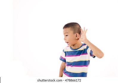 Curious Disappointed boy listens. Closeup portrait child hearing something, parents talk, hand to ear gesture isolated grey background. Human face expression, emotion, body language, life perception