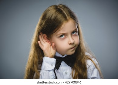 Curious Disappointed girl listens. Closeup portrait child hearing something, parents talk, hand to ear gesture isolated grey background. Human face expression, emotion, body language, life perception