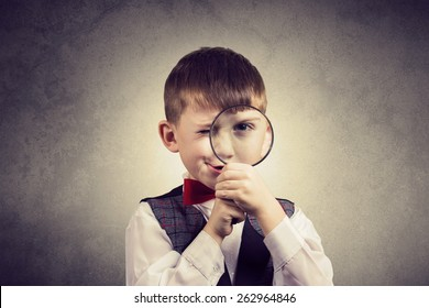 Curious Exploring little boy with magnifying glass, on yellow background.