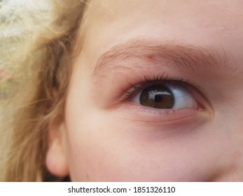 A curious eye in a young girl's face