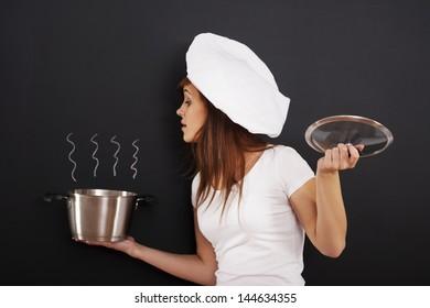 Curious female chef peeking into the pot