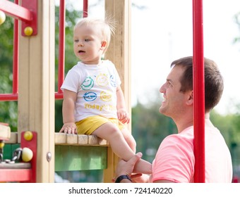A curious, funny, joyful toddler son and a single, strong father playing on a playground on a blurred natural background.