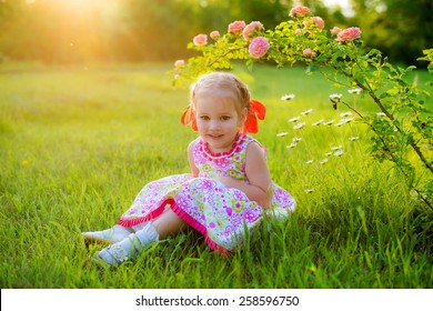 curious girl in beautiful summer dress with a red bow on her head in the spring park sitting on the grass under a bush