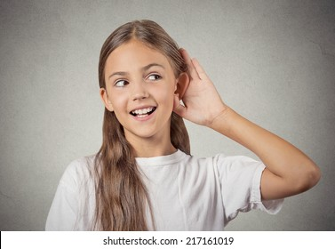 Curious girl listens. Closeup portrait teenager hearing something, parents talk, hand to ear gesture isolated grey wall background. Human face expression, emotion, body language, life perception