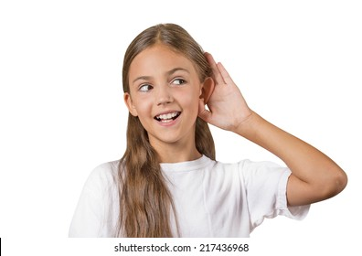 Curious girl listens. Closeup portrait teenager hearing something, parents talk, hand to ear gesture isolated white background. Human face expression, emotion, body language, life perception