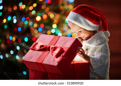 Curious girl in Santa cap looking into open giftbox with unusual present
