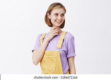 Curious girl stopping by cafe, smelling great scent of bakery, turning right and smiling with intrigued and joyful expression, touching chin, being interested in something, thinking over gray wall