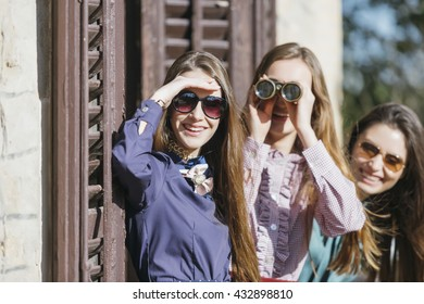 Curious girlfriends standing on balcony and spying through binoculars.