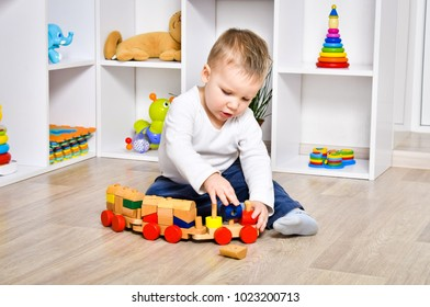 Curious handsome child playing with a wooden train