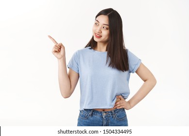 Curious happy friendly-looking pretty asian girl acne prone skin look away intrigued pointing gazing left interested picking making choice cool store asking merchant question hold hand waist