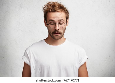 Curious intelligent male wears round spectacles, casual t shirt, notices something down, concentrated on floor, has puzzled look, isolated over white studio background. People and facial expressions