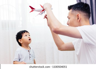 Curious kid looking at the plane toy and playing with father. Asian family playing toys together at home
