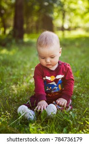 curious kid sits on the green grass and is surprised