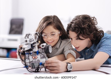 Curious kids playing with robot at school