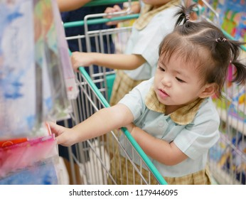 Curious little Asian baby girl, 18 months old, in a shopping trolley irresistibly grasping stuff in her reach while her mother is doing a shopping