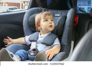 Curious little baby boy sitting in safety car seat and looking around with interest.  Traveling with baby concept. Child transportation safety.