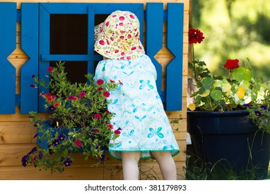 curious little baby girl looking to the window of wooden kids playhouse in the garden with blooming summer flowers