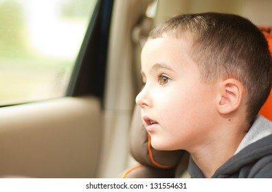 Curious little boy in the car watching the window sitting in safe chair
