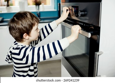 Curious little boy dangerously playing with the knobs on the oven. Danger at home