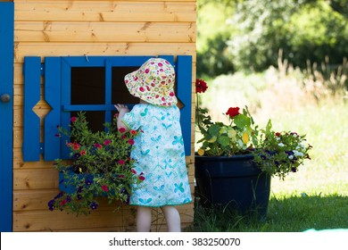 curious little cute girl in blue dress looking in the wooden garden play house with blue windows and blooming flowers in the summer