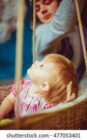 Curious little girl looks at the balloon while sitting in the basket