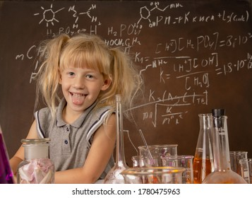 Curious little girl with test tubes and colorful substances making tests anf keeping her toungue ou at school laboratory. Small kid learning chemistry and conducts science experiment on biology lesson