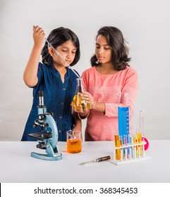 Curious little Indian school girls or scientists studying science, experimenting with chemicals or microscope at laboratory, selective focus