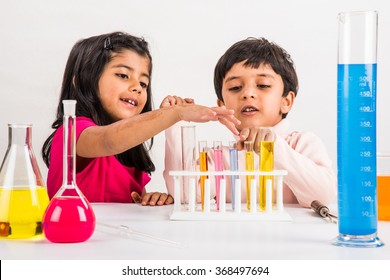 Curious little Indian school kids or scientists studying science, experimenting with chemicals or microscope at laboratory, selective focus