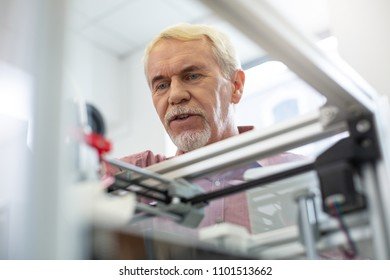 Curious look. Handsome senior man peeking inside 3D printer while watching it working smoothly