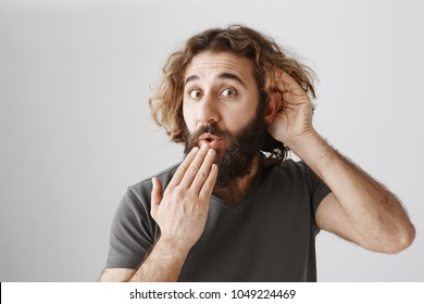 Curious man eavesdropping behind door. Studio shot of handsome intrigued eastern guy who likes rumors overhearing conversation, holding hands near ear and mouth, being amazed with news