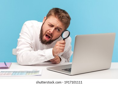 Curious man office worker looking at laptop display through loupe, spying trying to find out private secure information, controlling internet connection. Indoor studio shot isolated on blue background